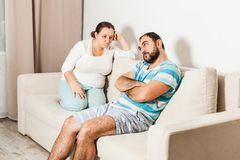 Couple sitting on couch at home in the living room. royalty free stock photos