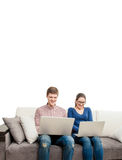 Couple sitting on couch with laptops Stock Photo
