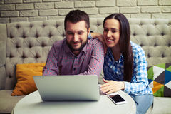 Couple sitting on couch and looking at laptop Royalty Free Stock Image