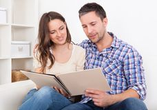 Couple sitting on couch looking at photo album Royalty Free Stock Images