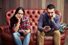 Couple sitting on couch looking at their phones stock photos