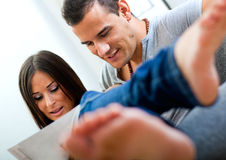 Couple sitting on couch and rea Stock Images