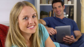 Couple sitting on couch smiling Royalty Free Stock Image
