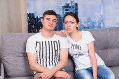 Couple sitting on a couch together Stock Photos