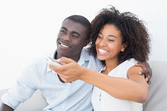 Couple sitting on couch together watching tv Stock Photos