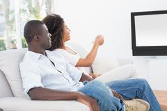 Couple sitting on couch together watching tv Stock Image