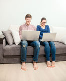 Couple sitting on couch and using laptops Royalty Free Stock Photography