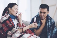 The couple is sitting on the couch wrapped in blankets. Man and woman are sick. The man has a sore throat. The couple is sitting on the couch wrapped in blankets Stock Photo