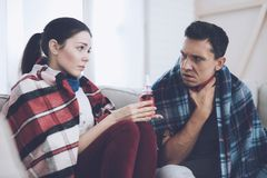 The couple is sitting on the couch wrapped in blankets. Man and woman are sick. The man has a sore throat. The couple is sitting on the couch wrapped in blankets Stock Photography