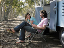 Couple Sitting On Deck Chairs Beside Campervan Royalty Free Stock Image