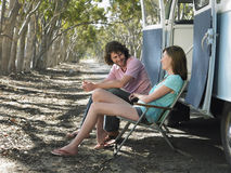 Couple Sitting On Deck Chairs Beside Campervan Stock Image