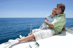 Couple sitting on deck of sailing boat out to sea, arms around each other, man holding rope, smiling, side view Stock Photography