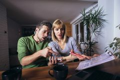Couple sitting at the desk at home read notice paper check bills or bank account balance. Couple sitting at the desk read notice paper check bills or bank royalty free stock photography