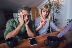 Couple sitting at the desk at home read notice paper check bills or bank account. Balance royalty free stock images