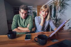 Couple sitting at the desk at home read notice paper check bills or bank account. Balance stock photo