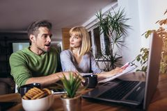 Couple sitting at home read notice paper check bills or bank account balance. Couple sitting at the desk at home read notice paper check bills or bank account royalty free stock image
