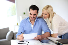 Couple sitting at desk and working together Stock Images