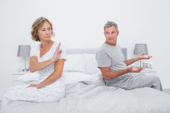 Couple sitting on different sides of bed having an argument Stock Photography