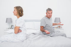 Couple sitting on different sides of bed having a dispute Stock Image