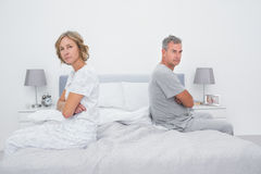 Couple sitting on different sides of bed not talking after argument. Looking at camera in bedroom at home royalty free stock image