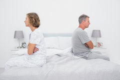 Couple sitting on different sides of bed not talking after dispu Royalty Free Stock Images