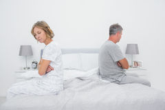 Couple sitting on different sides of bed not talking after fight. In bedroom at home Stock Images