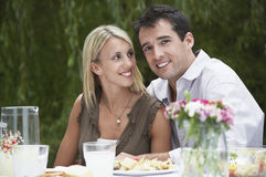 Couple Sitting At Dining Table In Garden Stock Images