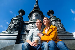 Couple sitting in Dresden Theaterplatz on statue Stock Images