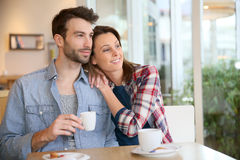 Couple sitting and drinking coffee in coffee shop Stock Photos