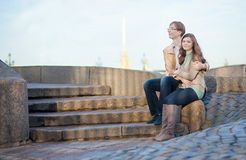 Couple sitting on the embankment Stock Photography