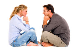 Couple sitting face to face. In white background Royalty Free Stock Photo