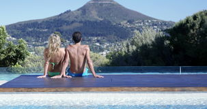 Couple sitting with feet in the pool. Rear view of couple sitting with feet in the pool stock video footage