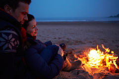 Couple Sitting By Fire On Winter Beach Royalty Free Stock Photography