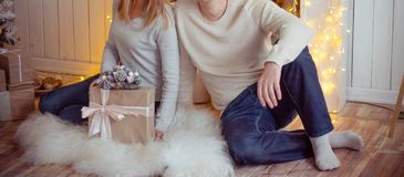 couple sitting by the fireplace on white fur, next to gifts and a Christmas tree royalty free stock image