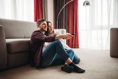 Couple sitting on the floor hugs and watch movie. Couple sitting on the floor against couch hugs and watch movie with popcorn at home, men with remote control in royalty free stock photos