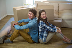 Couple sitting on the floor back to back. At home Royalty Free Stock Image