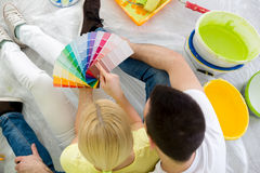 Couple sitting on floor and choosing color for painting Stock Photo