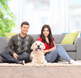 Couple sitting on the floor with a dog at home Royalty Free Stock Photography