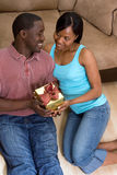Couple Sitting On Floor Holding Gift Box-Vertical Royalty Free Stock Photos