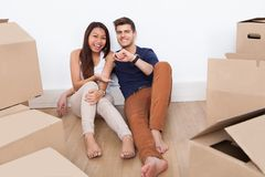 Couple Sitting On Floor Holding Keys From Their New Home Royalty Free Stock Image