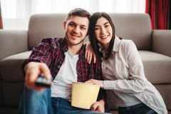 Couple sitting on the floor hugs and watch movie. Couple sitting on the floor against couch hugs and watch movie with popcorn at home, men with remote control in royalty free stock images