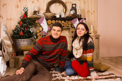 Couple Sitting on Floor inside Log Cabin in Winter Stock Photography