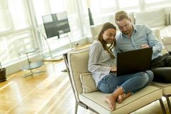 Couple sitting on the floor with laptop in the living room royalty free stock image