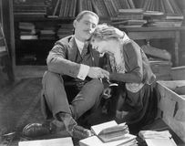 Couple sitting on the floor of a library holding each other Royalty Free Stock Images