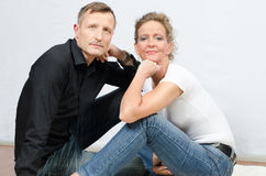 Couple sitting on the floor looking into camera Stock Photos