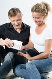 Couple sitting on the floor looking at photos Stock Photography