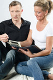 Couple sitting on the floor looking at photos.  Stock Photos