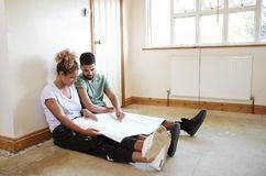 Couple Sitting On Floor Looking At Plans In Empty Room Of New Home royalty free stock photography