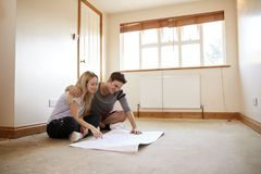 Couple Sitting On Floor Looking At Plans In Empty Room Of New Home royalty free stock photos