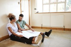 Couple Sitting On Floor Looking At Plans In Empty Room Of New Home stock images